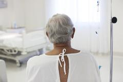 Older patient wearing gown in hospital room - stock photo