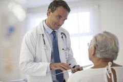 Doctor talking to older patient in hospital - stock photo