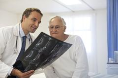 Doctor and patient examining x-rays in hospital room - stock photo