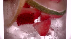 Drinking glass with Fruit, ice cubes floating in Sparkling water Stock Footage