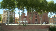 Trees by river in old town Perpignan, monumental tower Stock Footage