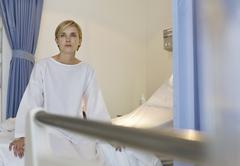 Patient sitting on hospital bed - stock photo