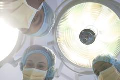 Surgeons bent over patient on operating table - stock photo