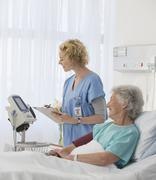 Nurse checking equipment in aging patient's hospital room Stock Photos