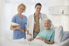 Doctor, nurse and senior patient smiling in hospital room - stock photo