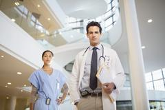 Portrait of confident doctor and nurse in hospital atrium - stock photo
