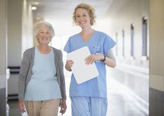 Portrait of smiling nurse and senior patient in hospital corridor Kuvituskuvat