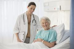 Portrait of doctor and aging patient in hospital room - stock photo