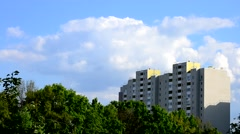 Beautiful cumulus clouds move behind modern high rise building Stock Footage