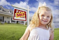 Cute Smiling Girl in Front Yard with Sold For Sale Real Estate Sign and House - stock photo