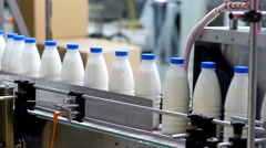 Plant production of milk and dairy products - white bottles on conveyor belt  Stock Footage