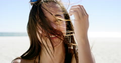 Close up portrait of beautiful young woman running hand through hair blowing in Stock Footage
