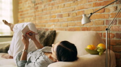 Woman lying on the sofa and writing notes in notebook Stock Footage
