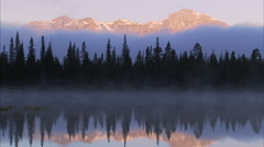 Morning light on mountain range with forest and misty lake Stock Footage