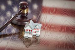 Small House and Gavel on Wooden Table with American Flag Reflection. Stock Photos