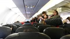 Inside AirAsia plane boarding time, stewardess picks a suitcase luggage rack Stock Footage