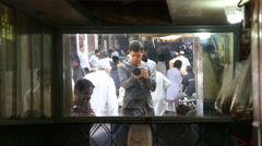 Man taking a photo of crowded street in Varanasi in mirror reflection. Stock Footage