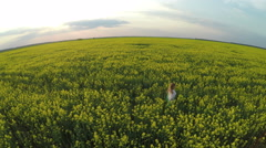 Girl running in Brassica rapa field at sunset - aerial view - stock footage