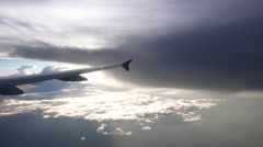 Aircraft fly away from dark cloud, bright sunny area ahead and downwards Stock Footage