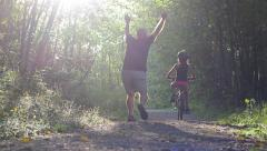 Excited Father Helping Daughter Ride Bike Down Forest Path Stock Footage