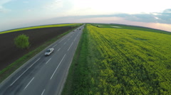 Countryside road next to Brassica rapa field at sunset - aerial view Stock Footage