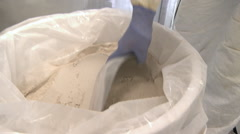 Closeup tilt shot of person scooping powder into a funnel. Stock Footage