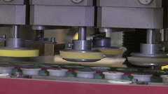 Closeup shot of rollers and plastic container tops. - stock footage