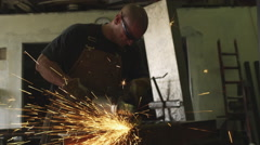 Handheld shot of carpenter grinding metal in his workshop Stock Footage
