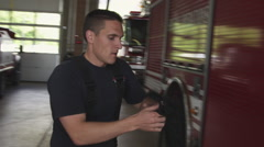 Handheld shot of a fireman getting ready to go out on an emergency call Stock Footage