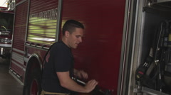 Slow motion handheld shot of fireman doing routine maintenance on fire truck in Stock Footage