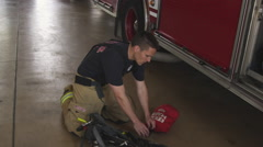 Handheld shot of fireman doing routine maintenance check on breathing apparatus Stock Footage