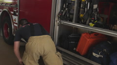 Slow motion handheld shot of fireman doing routine maintenance check on Stock Footage