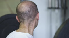 Close-up handheld shot of a man weightlifting at a gym Stock Footage