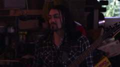 Handheld shot of a long-haired man playing a bass guitar Stock Footage
