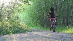 Asian Girl Rides Bike Down Pretty Forest Path Alone Stock Footage