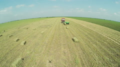 Stock Video Footage of Aerial shot over harvesting and baling alfalfa or Lucerne with tractor