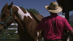 Slow handheld shot of a cowboy saddling a horse Stock Footage