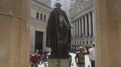 Tourists walk past a statue of George Washington at Wall Street in New York Stock Footage