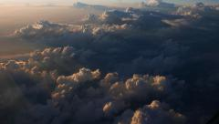 Mysterious cumulus clouds darken the bottom, sunset time, aircraft window view Stock Footage