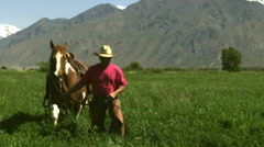 Slow handheld shot of a cowboy guiding his horse on the meadow Stock Footage