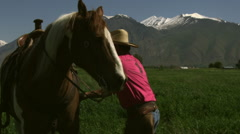Slow handheld shot of a cowboy getting on his horse Stock Footage
