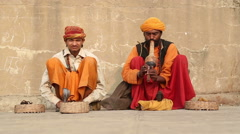Two Indian men hypnotising a snake with music at street in Varanasi. - stock footage