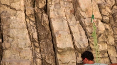 Tilt shot of a rock-climber pulling up his partner's rope. Stock Footage