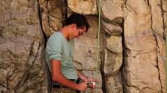 Tilt shot of a man adjusting a locking carabiner. Stock Footage