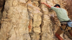 Handheld shot of a rock-climber climbing a cliff. Stock Footage