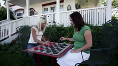 Tracking shot of two women playing checkers. - stock footage