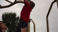Tracking shot of a small boy hanging from monkey bars with help from his mother. Stock Footage