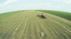 Aerial shot over harvesting and baling alfalfa or Lucerne with tractor Stock Footage