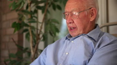 A close up shot at an angle of an elderly man speaking. - stock footage