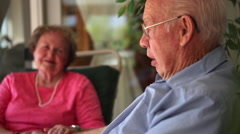 A shot of an elderly man and woman laughing as they tell a story. Arkistovideo